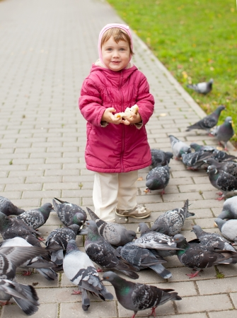 life jacket: two-year girl feeding pigeons  in the park