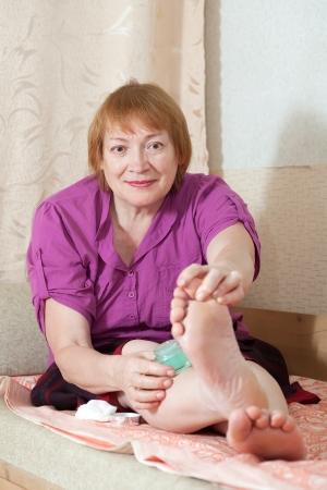Mature woman caring for the nails on your feet Stock Photo - 16243421