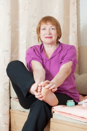 Mature woman treats her toenails Stock Photo - 16243422