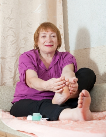 foot fungus: Mature woman looks at her toenails Stock Photo