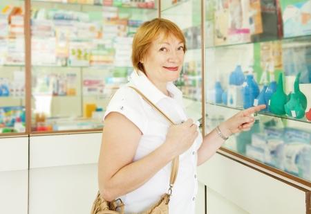 einlauf: Ältere Frau wählt Einlauf in der Apotheke