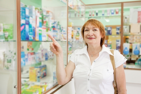 Mature woman chooses drugs at the pharmacy photo