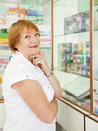 Mature woman chooses contraceptives at the pharmacy photo