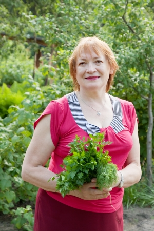 dill and parsley: Mature woman with harvested dill and parsley  in garden