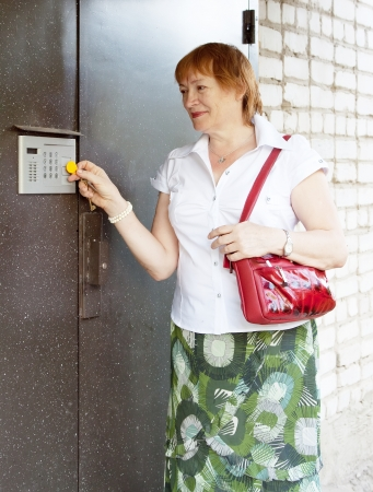 access control: Mature woman opening door with electronic key