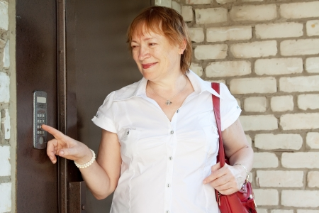 pushing the button: Mujer madura presionando el bot�n de la casa de intercomunicaci�n