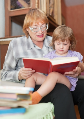 grandmother and child reading  book together on couch in home Stock Photo - 16243417