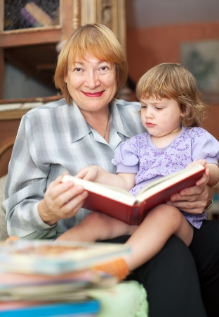 grandmother and baby girl reading book in home Stock Photo - 16243414