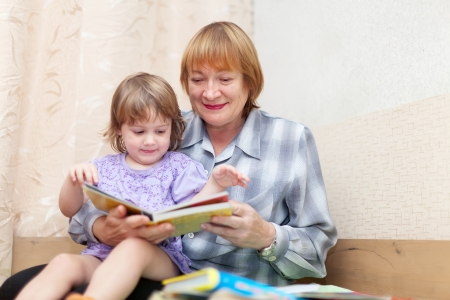 Woman and baby girl reading book in home Stock Photo - 16243452