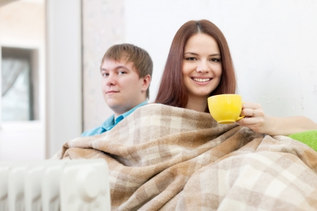 Couple relaxing near warm radiator  in home Stock Photo