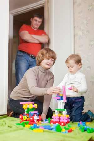 parents and child plays with meccano set in home photo