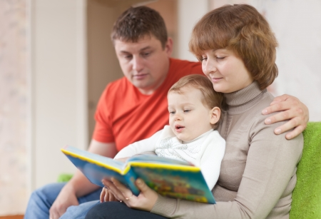 Happy parents with child looks the book in home interior Stock Photo - 16274424