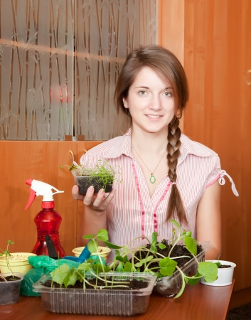 Young woman with vaus seedlings at home Stock Photo - 16331060