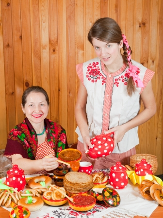 Happy mother with teenager daughter eating pancake with caviare during  Shrovetide Stock Photo - 16331083