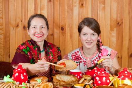 sudarium: Women in traditional  clothes eating pancake with caviare during  Shrovetide