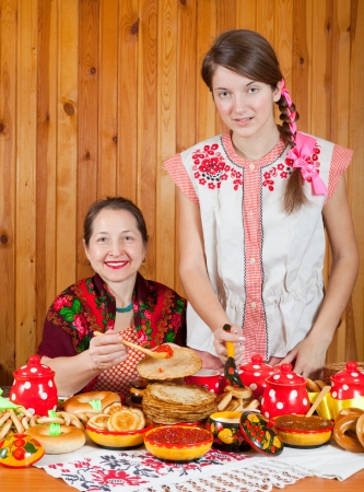 sudarium: Happy mother with teenager daughter eating pancake with caviare during  Shrovetide