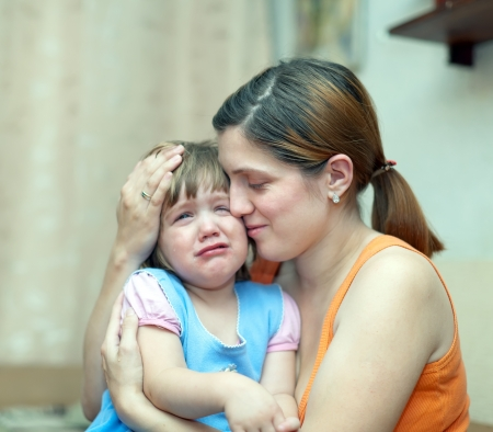 berate: woman soothes crying daughter. Focus on woman