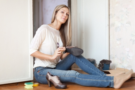 Woman sits on floor and cleans shoes Stock Photo - 16326878