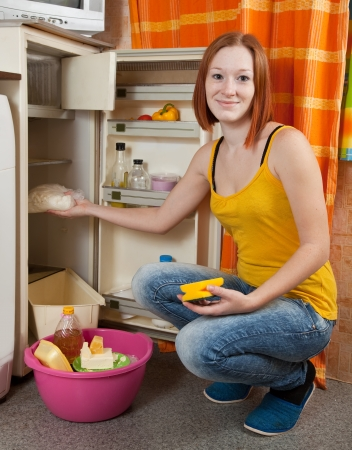 Young woman  defrosting the refrigerator at her kitchen photo