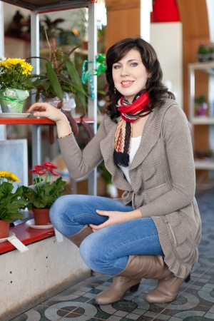 woman in flower shop near the shelves with flower pots Stock Photo - 16374663