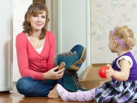 Woman with baby girl sits on floor and cleans footwear photo