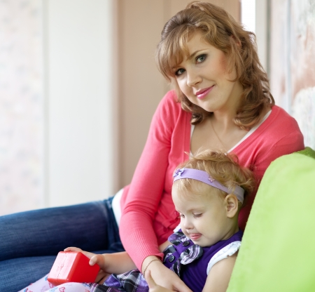 Happy mother with her baby   in home interior photo