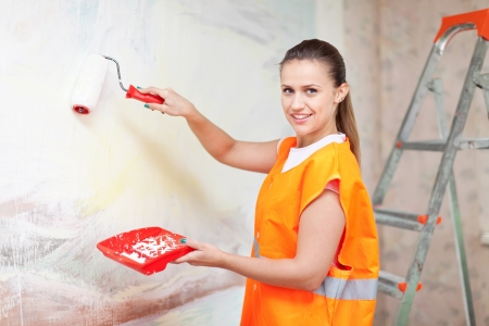 priming brush: Female house painter paints wall with roller
