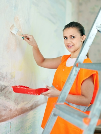 priming brush: Female house painter paints wall with brush