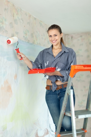 Happy woman paints wall with roller at home Stock Photo - 16433828