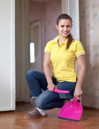 Woman sweeping the floor at home photo