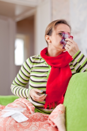 sick woman uses handkerchief in home Stock Photo