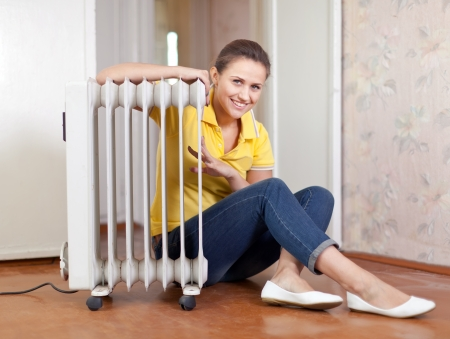 calorifer:  smiling woman  near warm radiator  in home Stock Photo