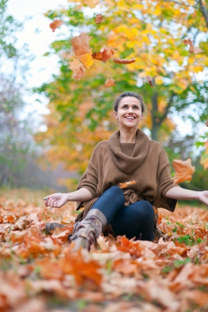 happy seasonable: Happy woman throws autumn leaves in the park
