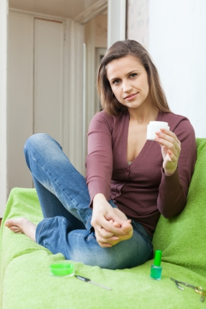 Beautiful woman puts cream on foot at her home Stock Photo - 16433762