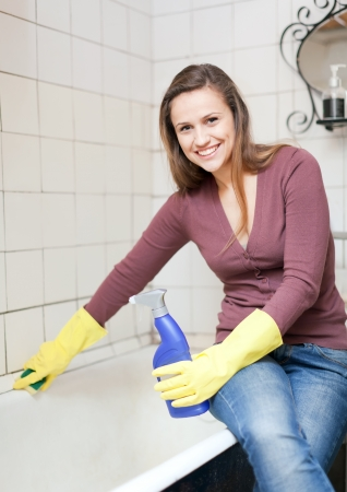 Smiling girl cleans bathtub in bathroom at home Stock Photo - 16433749