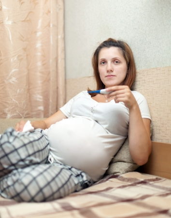 pregnant woman holding thermometer in home photo