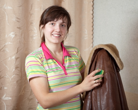 Woman cleaning leather jacket  with sponge  at home photo
