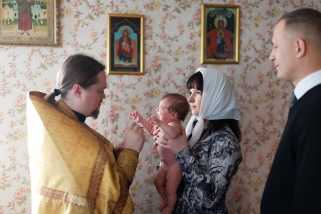 VLADIMIR,RUSSIA  - NOVEMBER 14: Baby being baptized at Sretenskaya church on November 14, 2012 in Vladimir, Russia. Godmother holds baby. Child - daughter of photographer who gets religious name Elena