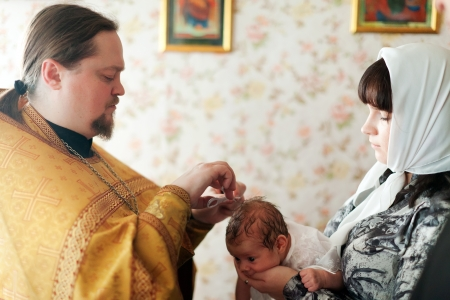 VLADIMIR, RUSSIA  - NOVEMBER 14: Priest at Sretenskaya church performing christening ceremony on November 14, 2012 in Vladimir, Russia. Child - daughter of photographer who gets religious name Elena