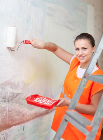 spalpeen: Female house painter paints wall with roller