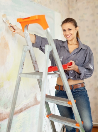 priming brush: Happy woman paints wall with brush Stock Photo