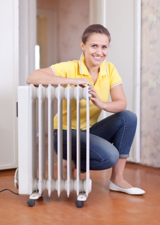 smiling woman  near warm radiator  in home Stock Photo