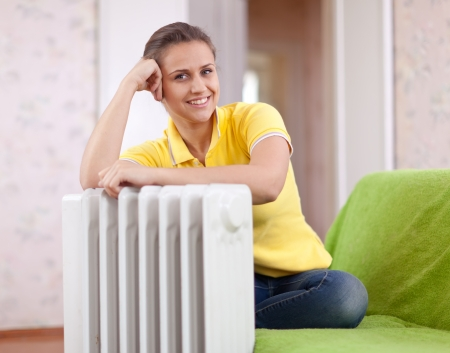 Happy woman near oil heater in home Stock Photo - 16516634