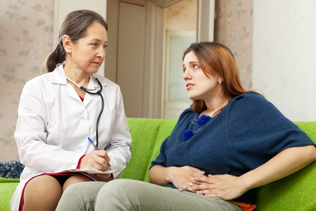 Woman complaining  to doctor about stomachache at home photo