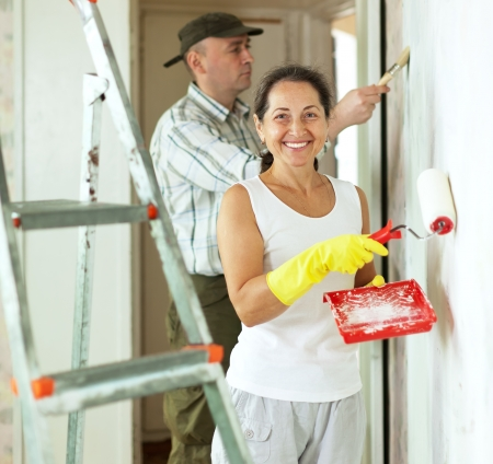 Smiling woman and man makes repairs in home photo