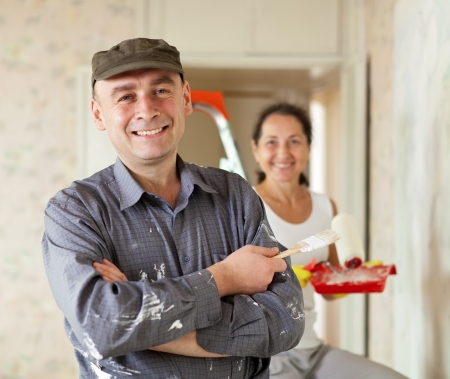 Happy man and woman paints wall at home together photo