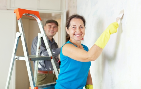 priming brush: Happy woman and man makes repairs in the apartment together Stock Photo