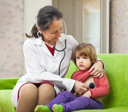 friendly mature childrens doctor examining 2 years child with  stethoscope at home photo