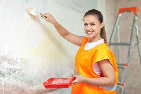 priming brush: Smiling woman in uniform paints wall with brush