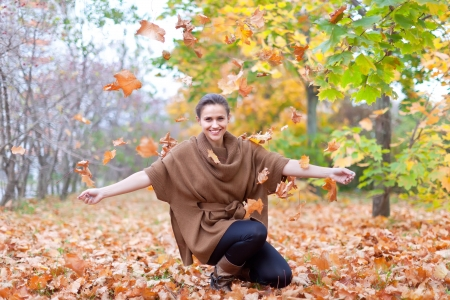 happy seasonable: Woman throws autumn leaves in the park